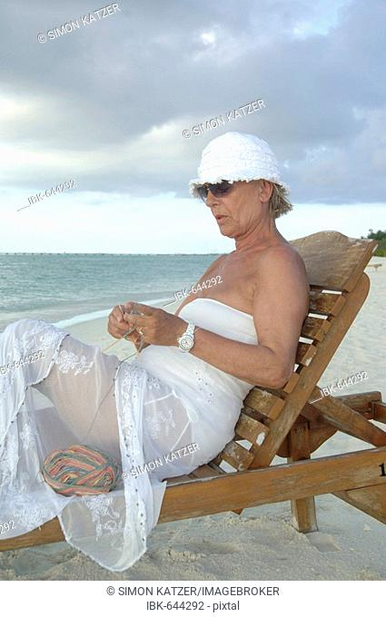Elderly woman knitting on the beach, Diffushi Island, Holiday Island, Southern Ari Atoll, Maldives, Indian Ocean