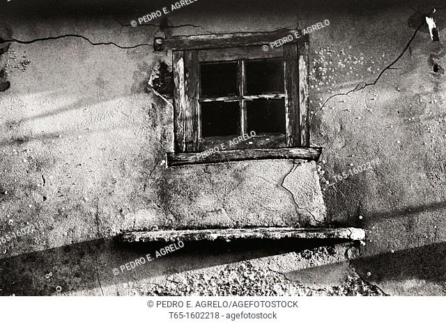 Broken window and wall of old abandoned house