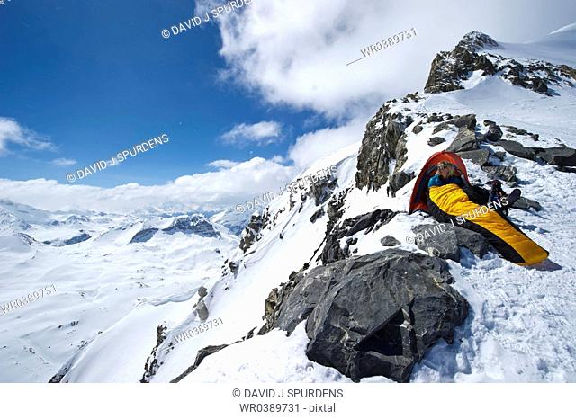 Mountaineer in sleeping bag at entrance to tent in high snowy mountains