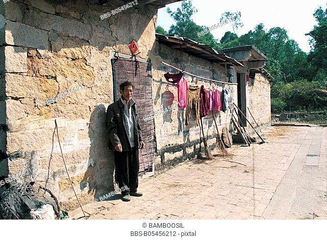 Senior man standing by residence in ancient Zhaojiabao Village, Zhangpu county, Zhangzhou city, Fujian Province, People's Republic of China