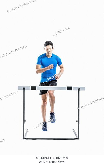 Male athlete running toward obstacle