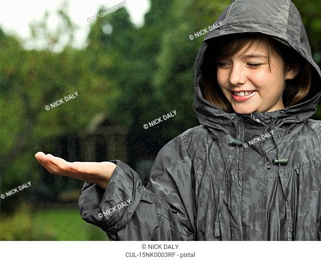 Girl holds hand out to catch rain