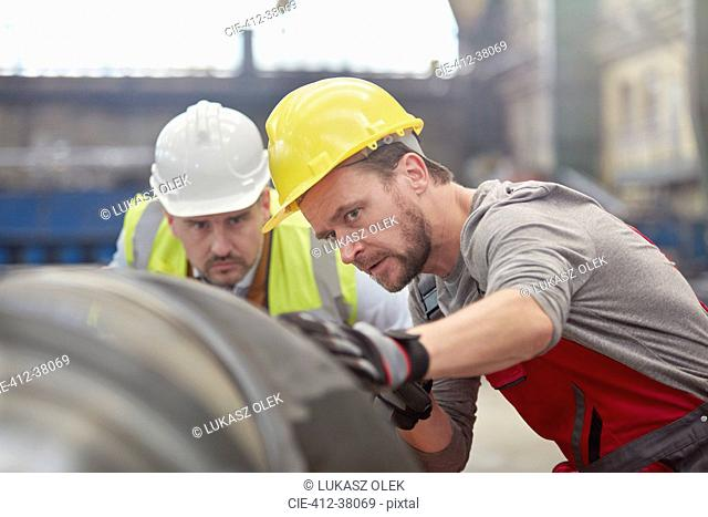 Focused male engineers examining steel part in factory