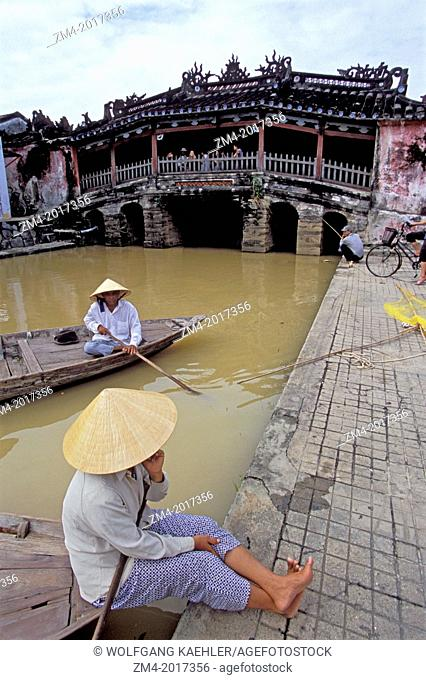 VIETNAM, HOI AN, BRIDGE PAGODA, LOCAL PEOPLE ON BOATS IN FOREGROUND