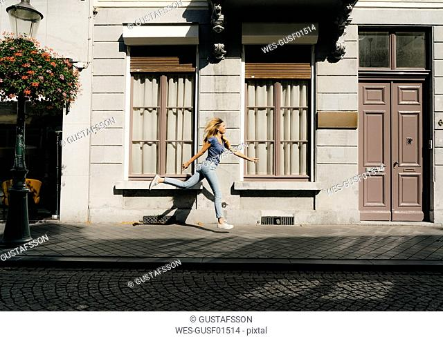 Netherlands, Maastricht, blond young woman running along building in the city