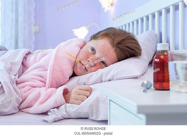 Girl lying in bed with thermometer in her mouth