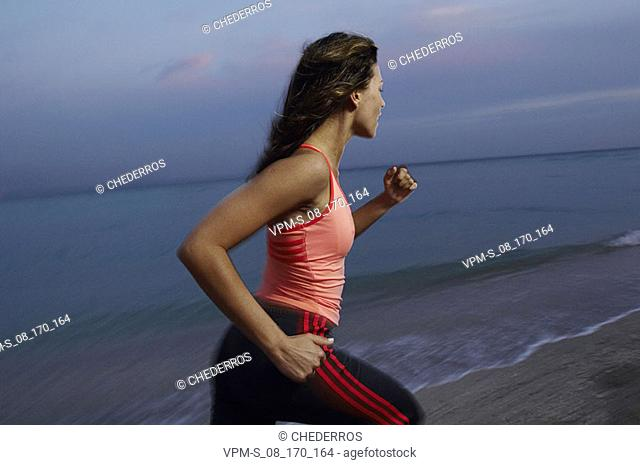 Side profile of a mid adult woman running on the beach