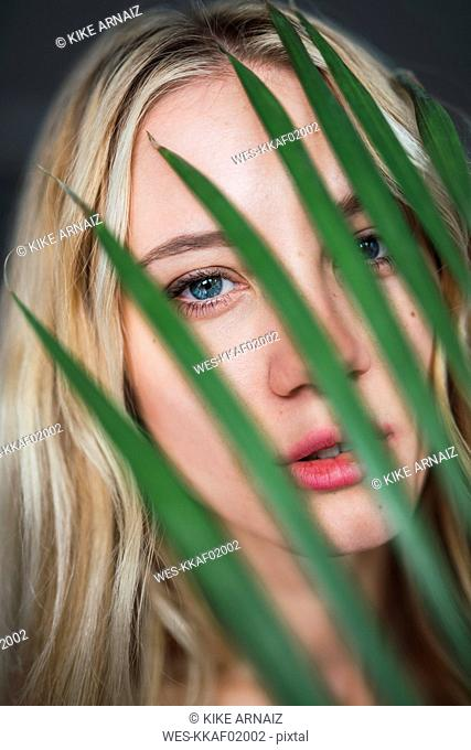 Portrait of young woman behind palm leaf