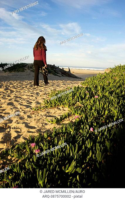 A women walking on the sand at Pismo Beach