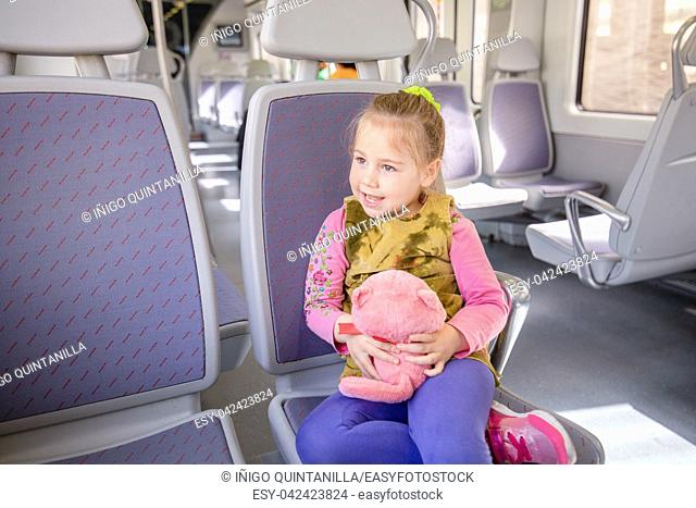 Four years old blonde cute girl, with a pink stuffed animal in hands, talking and sitting in public lonely train