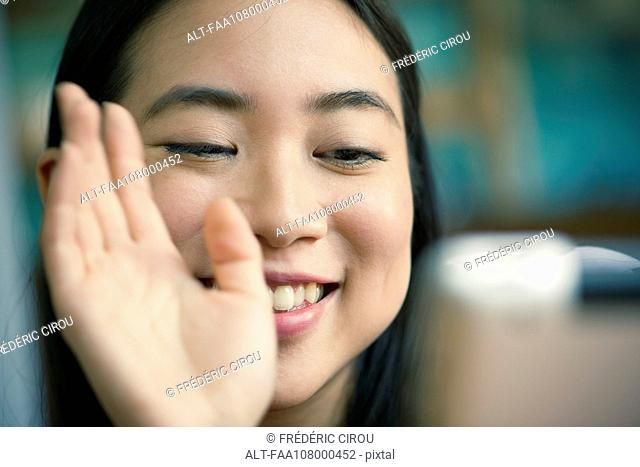 Young woman waving at camera while video conferencing on digital tablet