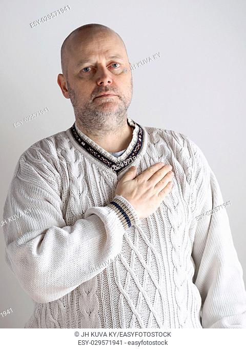 Portrait, casual looking caucasian male wearing a white pullover, right hand over heart and he looks toward the camera