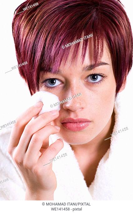 AE19HW Beautiful woman removing her make up with a cotton wool pad