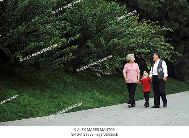 Older couple walking with grandson in the park