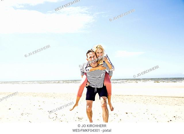 Happy playful couple on the beach