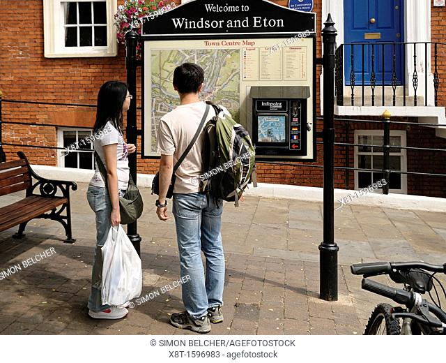 Couple Looking at a Street Tourist Information Point with a Map of Locations, Windsor and Eton, Berkshire, UK