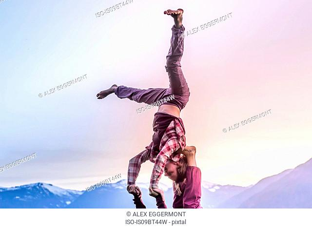 Two young women practicing acroyoga in front of mountain range at sunset, Squamish, British Columbia, Canada