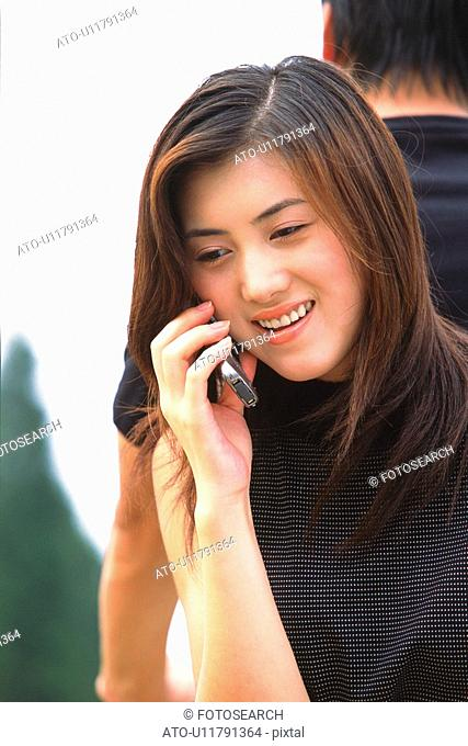 Image of a Young Adult Woman Talking on her Cell Phone Looking Down, Smiling, Front View
