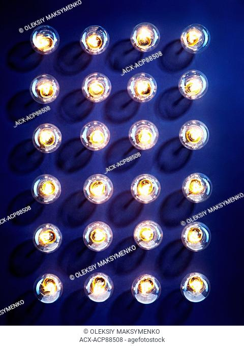 A group of illuminated incandescent light bulbs shining isolated on blue background