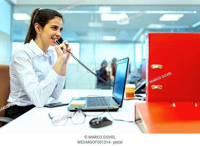 Young businesswoman talking on phone in an office