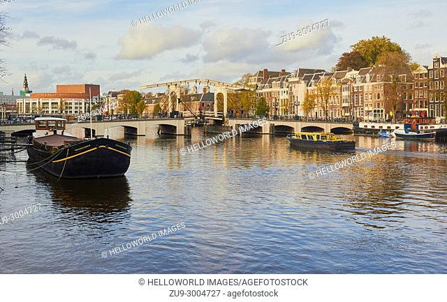 View along the Amstel River towards the Magere Brug (skinny bridge) a pedestrian and bicycle bascule bridge, Amsterdam, Netherlands