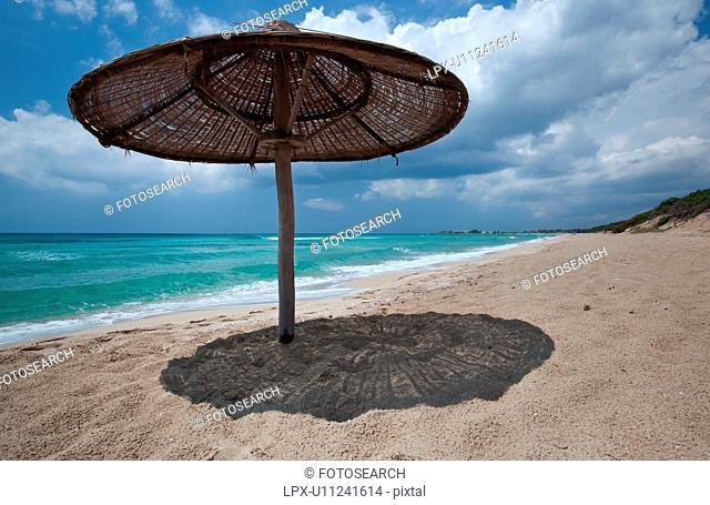 Empty, fine sandy beach , with single wicker beach umbrella casting shadow, white foam, green sea colour, blue sunny sky, with storm threatened, Salento, Puglia