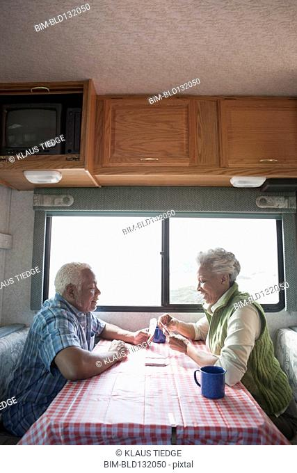 Mixed race Senior couple having coffee in RV