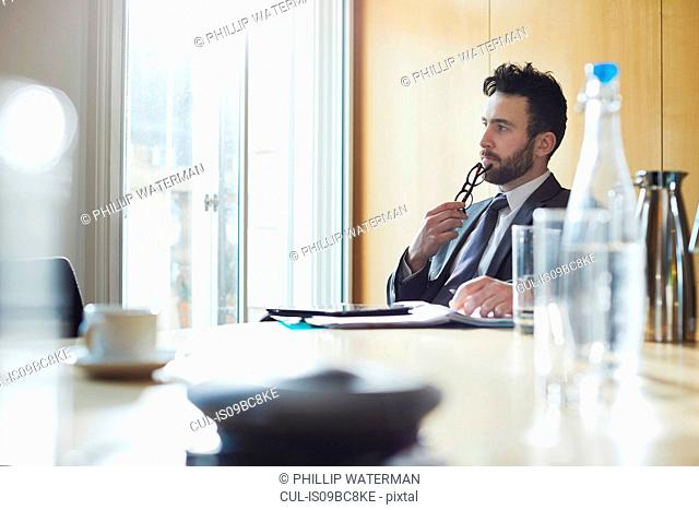 Businessman contemplating at boardroom table