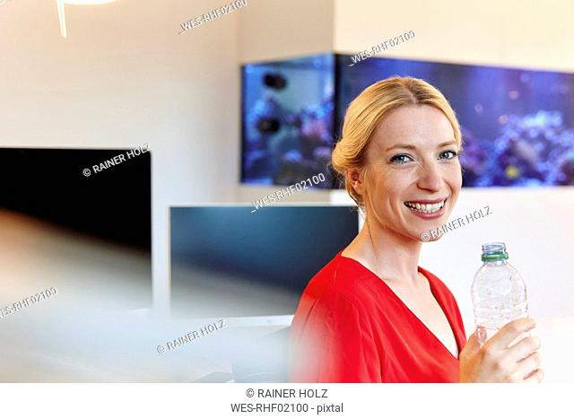 Portrait of smiling young woman drinking water from bottle in office