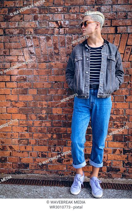 Man posing against brick wall