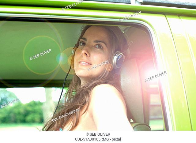 Woman listening to headphones in van