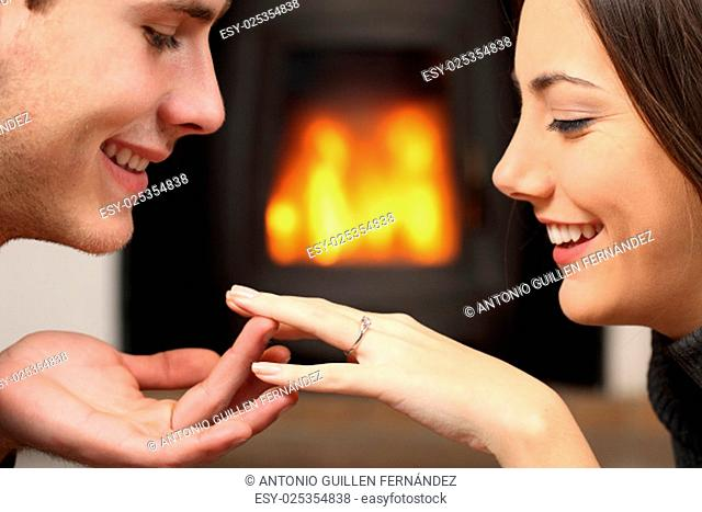 Couple looking a engagement ring after proposal at home with a fire place in the background