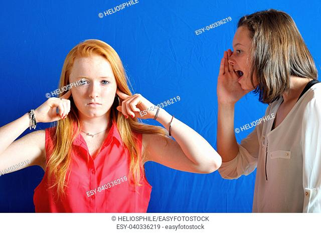 Two teen, one shouting the other plug her ears