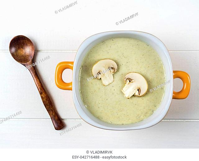 Yellow bowl cream soup of mushrooms with croutons on wooden table. Cream soup of mushrooms, potatoes and cream with spices. The view from the top