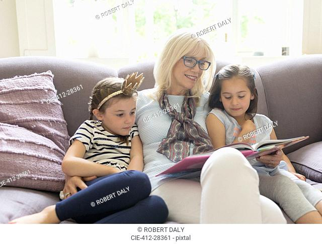 Grandmother and granddaughters reading book on living room sofa