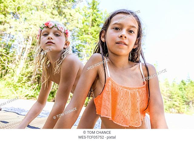 Portrait of two girls wearing flower crown and bikini outdoors in summer