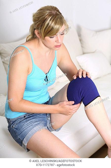 blonde woman sitting on sofa wearing bandage on knee