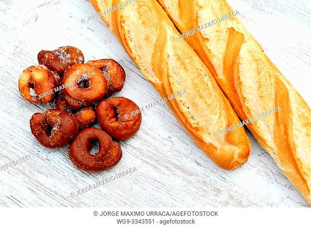 Two loaves of bread and ring doughnuts on a table
