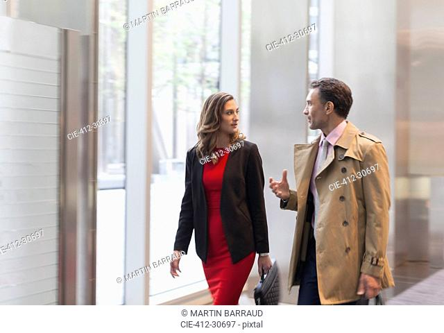 Corporate businessman explaining to businesswoman in office lobby
