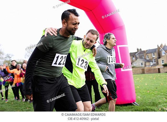 Man helping injured runner crossing finish line at charity run