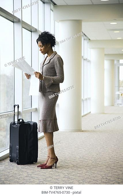 African businesswoman next to suitcase