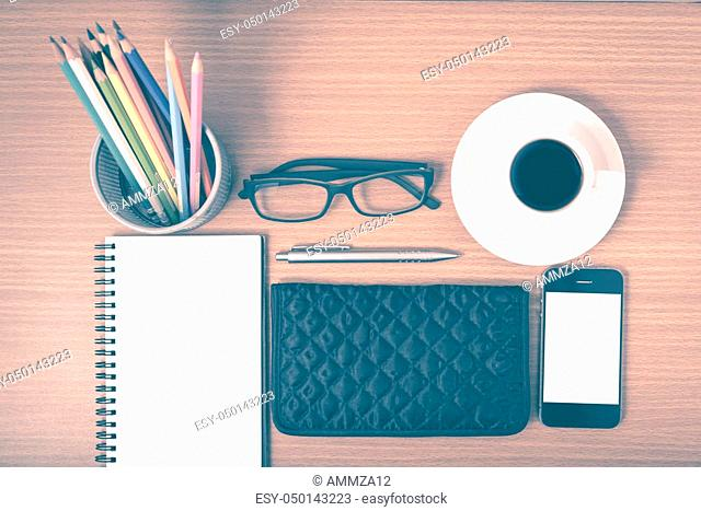 office desk: coffee with phone, notepad, eyeglasses, wallet, color pencil box on wood background vintage style