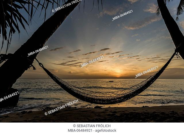 A hammock between two coconut trees in the famous Sumurtiga beach on the comfortable island Pulau Weh near Sumatra. In the background light mood at sunrise