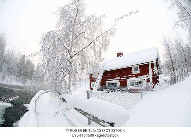 Locla house wooden built besides a frozen river in February, Kuusamo, Finland