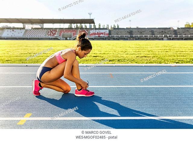 Female athlete tying shoes on race track