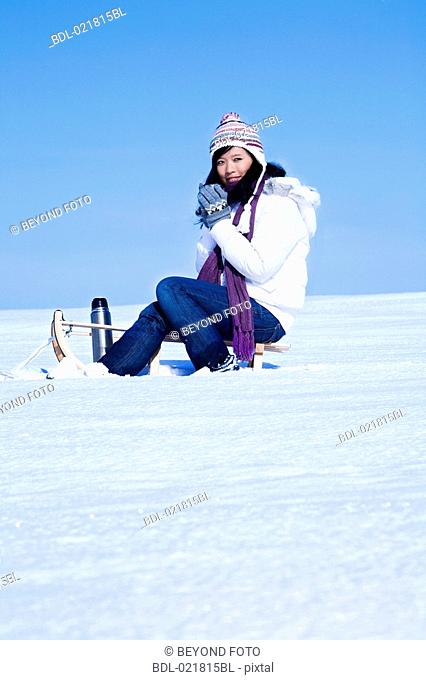 young asian woman sitting on sledge having drink from thermos bottle