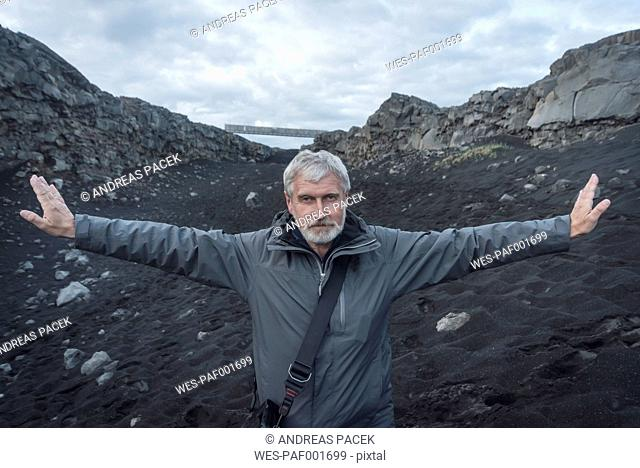 Iceland, Reykjanes, Senior man with arms outstretched, Mid-Atlantic Ridge