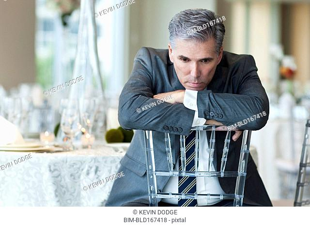 Caucasian businessman brooding in empty dining room