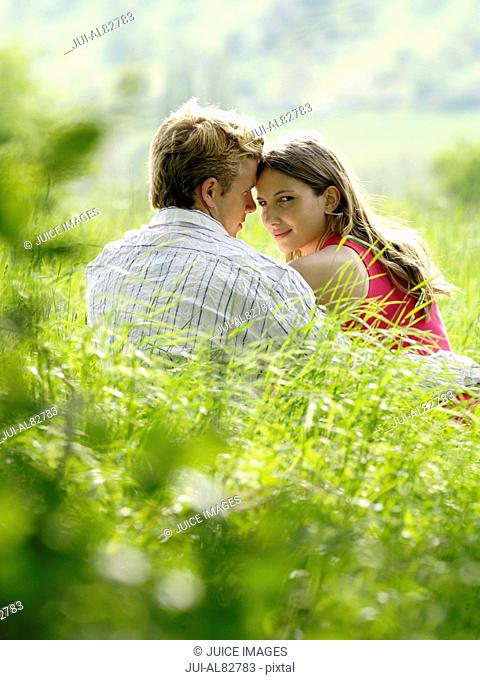 Couple touching foreheads and sitting in grass