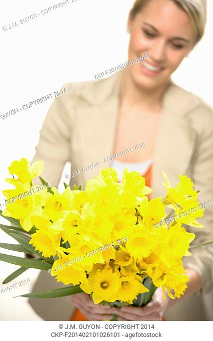 Bunch of yellow spring narcissus flowers smiling woman in background